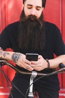Tätowierter mann, der das mobiltelefon sitzt auf fahrrad verwendet