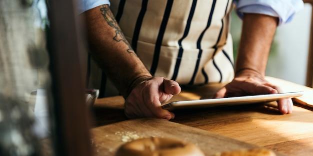 Tätowierter mann, der digitale tablette im shop des bäckers verwendet