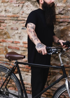 Tätowierter mann, der fahrrad gegen verwitterte backsteinmauer hält