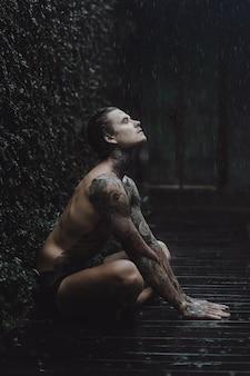 Tätowierter mann, der im regen aufwirft