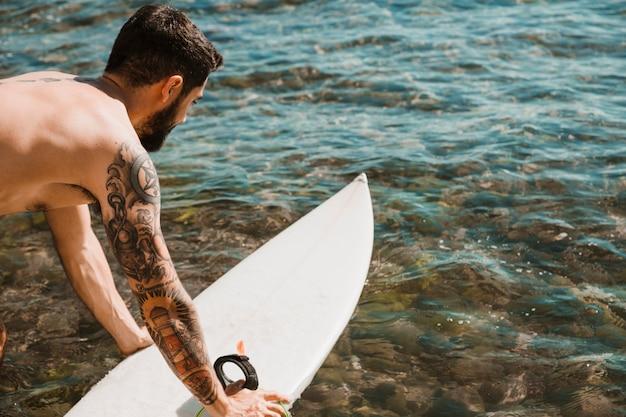 Tätowierter mann, der surfbrett auf wasser setzt