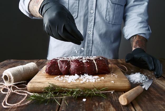 Tätowierter metzger in schwarzen handschuhen salzt gebundenes stück fleisch, um es zu rauchen.