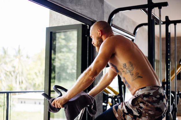 Tätowierter muskulöser starker bärtiger mann trainieren cardio auf fahrrad in der turnhalle nahe großem fenster mit blick auf bäume draußen
