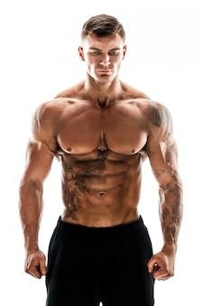 Tätowierter muskulöser superhöchster gutaussehender mann, der im studio lokalisiert auf weißer szene aufwirft