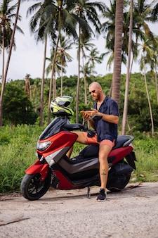 Tätowierter starker mann auf tropischem dschungelfeld mit rotem motorrad