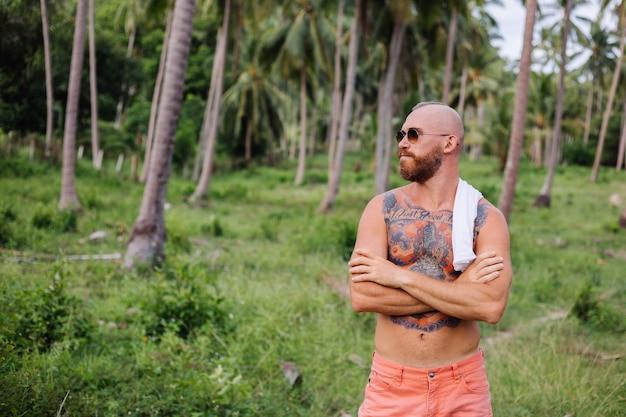Tätowierter starker mann auf tropischem dschungelfeld ohne hemd