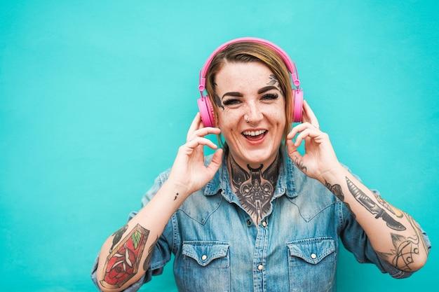 Tätowierungsmädchen, das musik mit kopfhörern hört