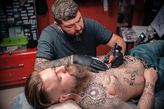 Tätowierungsmeister, der tätowierung im tätowierungsstudio tut. tätowierer, der tätowierungskunst in seinem salon macht.