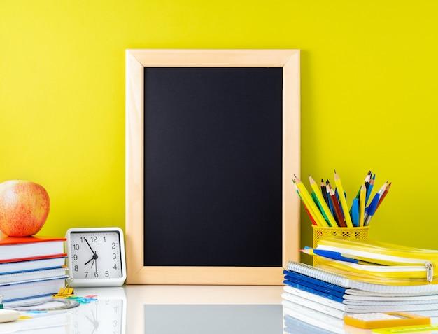Tafel, apfel und schulbedarf auf weißer tabelle durch die gelbe wand. seitenansicht, leer.
