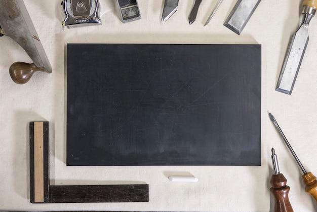Tafel für kreide auf einer werkbank und zimmereiwerkzeugen