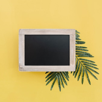 Tafel für Mock-up mit Palmblättern auf gelbem Hintergrund