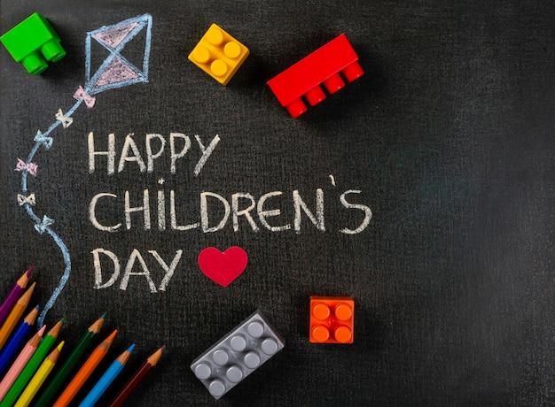Tafel geschriebener glücklicher tag und drachen der kinder, die mit zerstreuten versammlungsstücken und farbbleistiften zeichnen