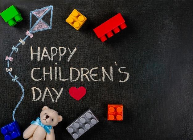 Tafel geschriebener glücklicher tag und karikaturdrachen der kinder mit zerstreuten bergen und teddybären