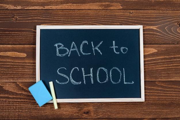 Tafel mit back to school text, kreide und schwamm auf einem holz.