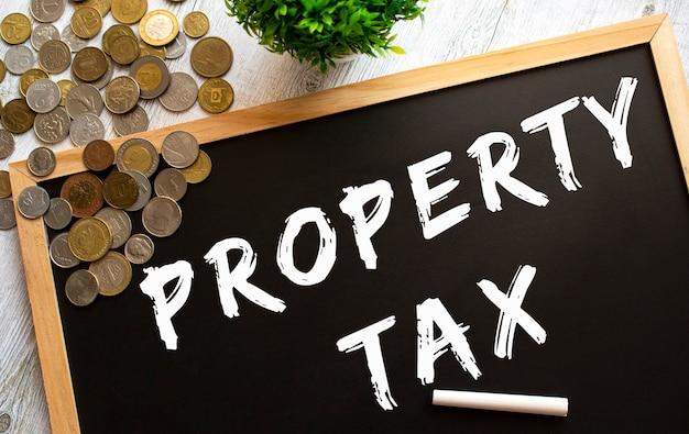 Tafel mit dem text property tax und metallmünzen auf einem grauen holztisch