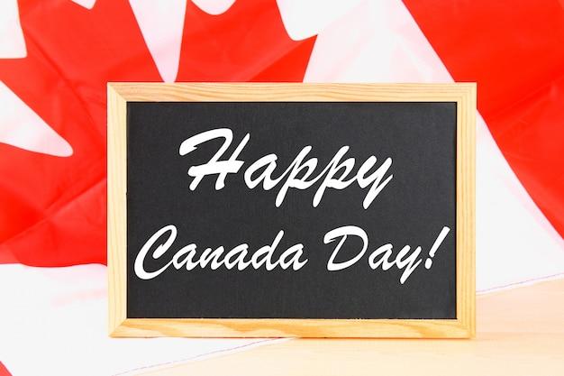 Tafel mit dem wort happy canada day auf der nationalflagge. fest am 1. juli.