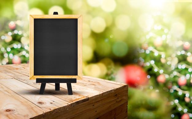 Tafel mit gestell auf hölzerner tabelle (nahrungsmittelstand) an unschärfe weihnachtsbaum-bokeh hellem hintergrund