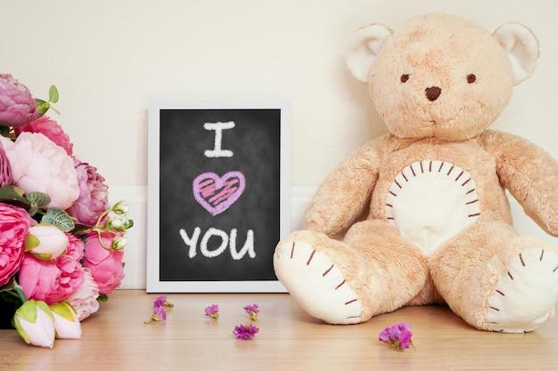 Tafel mit kreide-schreibwort ich liebe dich mit niedlichem teddybär und blume