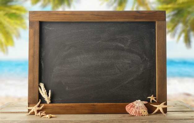Tafel mit muscheln und seesternen auf dem tisch vor dem hintergrund des meeresstrandes (ozean)