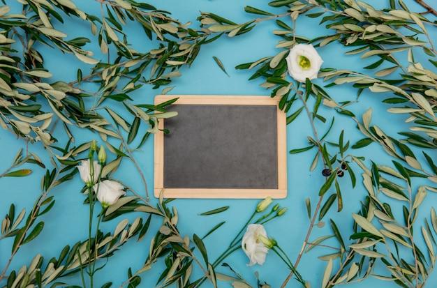 Tafel mit olivenzweigen auf blauem hintergrund. ansicht von oben