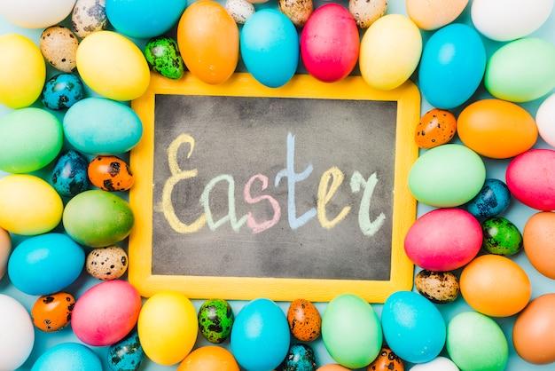 Tafel mit ostern-titel zwischen farbigen eiern