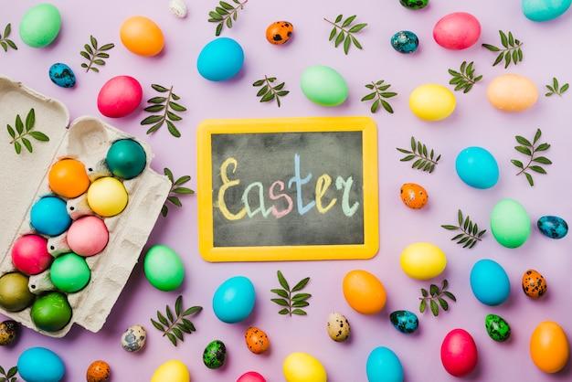 Tafel mit ostern-titel zwischen hellem satz farbigen eiern und blättern nahe behälter