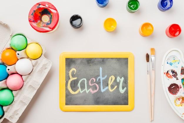 Tafel mit ostertitel in der nähe von farbigen eiern in behälter, pinsel, wasserfarben und farbpalette