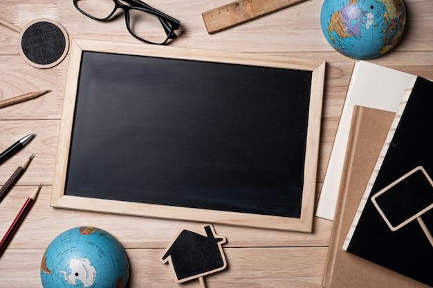 Tafel mit schulmaterial, globus, notizbuch und tafel auf einem holztisch