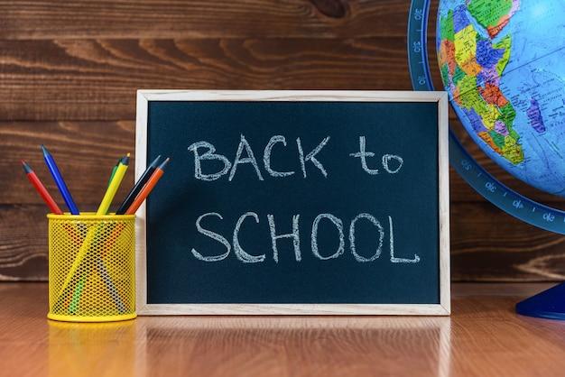 Tafel mit text back to school, satz buntstifte mit glas und globus auf hölzernem hintergrund