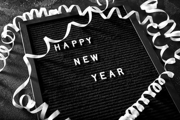 Tafel mit text happy new year auf dunkel