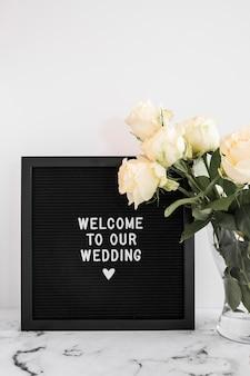 Tafel mit willkommen zu unserer hochzeitsbotschaft und rosenvase auf marmortischplatte