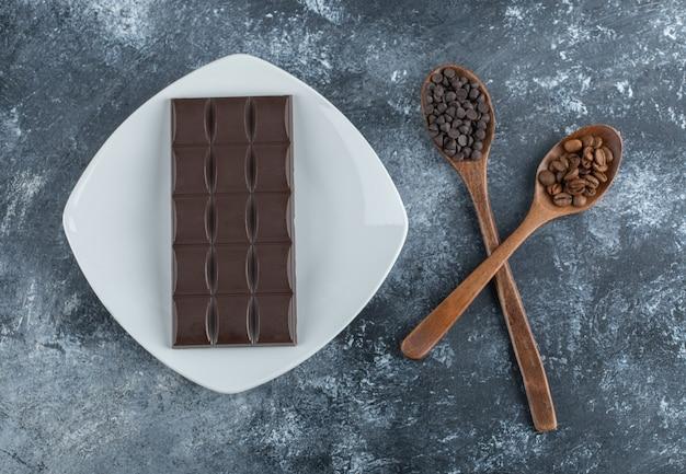 Tafel schokolade mit kaffeebohnen und schokoladenstückchen.