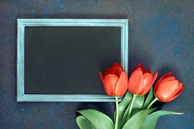 Tafel und bündel rote tulpen auf abstrakter dunkelheit, raum für ihren test