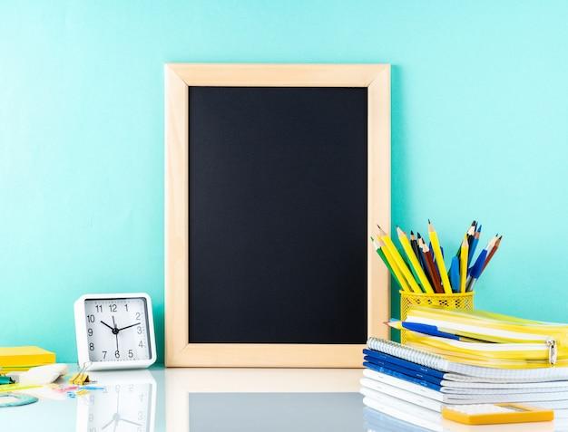 Tafel und schulbedarf auf weißer tabelle durch die blaue wand. seitenansicht, leer