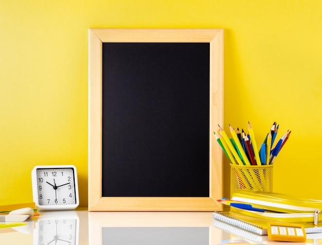 Tafel und schulbedarf auf weißer tabelle durch die gelbe wand. seitenansicht, leer
