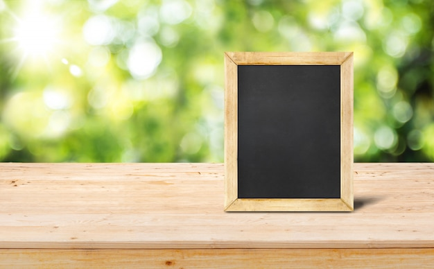 Tafelmenü auf hölzerner tischplatte (essensstand) mit verschwommenem gartengrün-naturbokeh