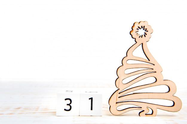 Tag 31 des monats, kalender auf weißem hintergrund mit hölzernem weihnachtsbaum.