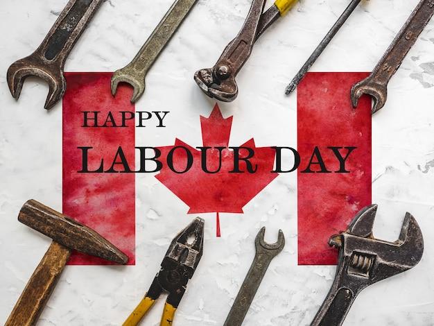 Tag der arbeit. handwerkzeuge, die vor dem hintergrund der kanadischen flagge liegen. ansicht von oben, nahaufnahme. vorbereitung auf die feier. herzlichen glückwunsch an familie, verwandte, freunde und kollegen