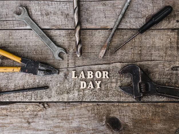 Tag der arbeit. handwerkzeuge und holzbuchstaben