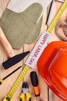 Tag der arbeit karte und ausrüstung. hammer, schutzhelm, arbeitshandschuhe. urlaub für arbeiter.
