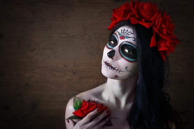 Tag der toten. halloween. junge frau am tag der toten maskenschädel-gesichtskunst und stieg. dunkler hintergrund.