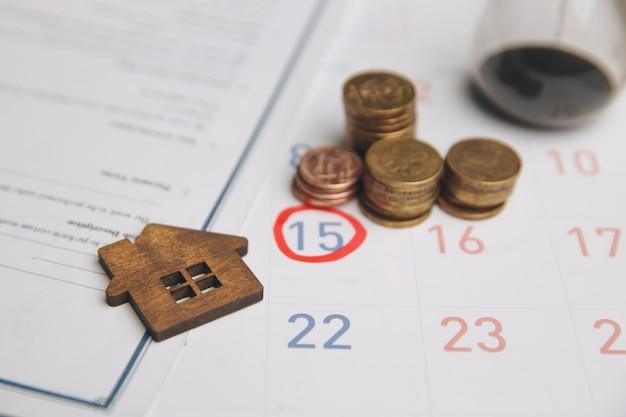 Tag des kaufs oder verkaufs eines hauses. tag der zahlung für miete oder darlehen. kalender und haus. es ist zeit, ihr haus zu versichern. leerraum für text.