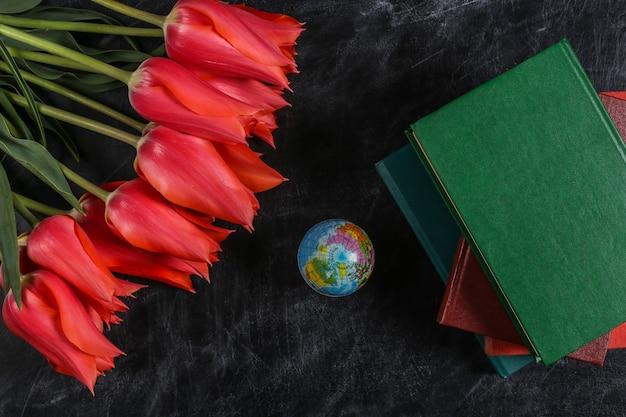Tag des lehrers oder tag des wissens. rote tulpen, stapel bücher, globus auf kreidetafel. ansicht von oben. zurück zur schule