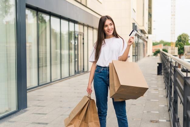 Tag einkaufen. volle länge der jungen frau, die einkaufstaschen hält und beim gehen entlang der straße lächelt