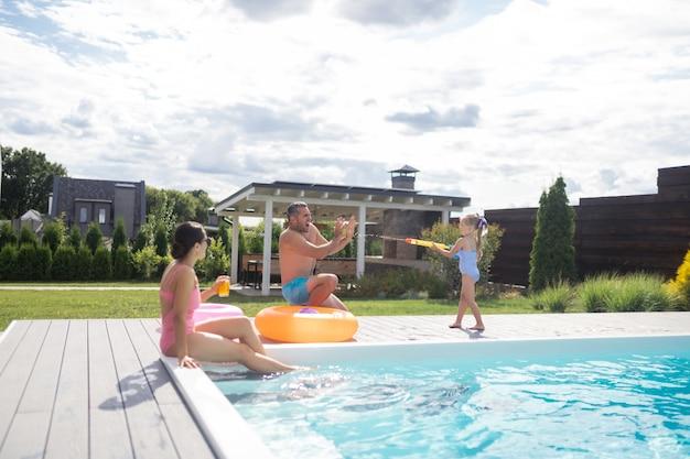 Tag in der nähe des pools. fröhliches süßes mädchen, das vater mit wasser spritzt, während es den tag in der nähe des pools verbringt?