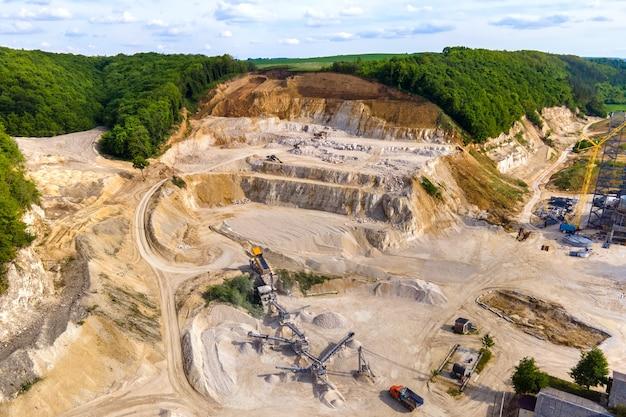 Tagebau von bausandsteinmaterialien mit baggern und muldenkippern am förderband.
