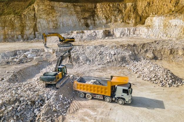 Tagebau von bausandsteinmaterialien mit baggern und muldenkippern.