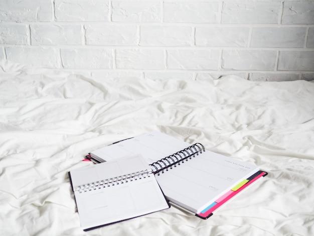 Tagebuch auf einem weißen tuch liegt, das konzept der fernarbeit, freiberuflich, arbeit von zu hause aus, komfort, blogger