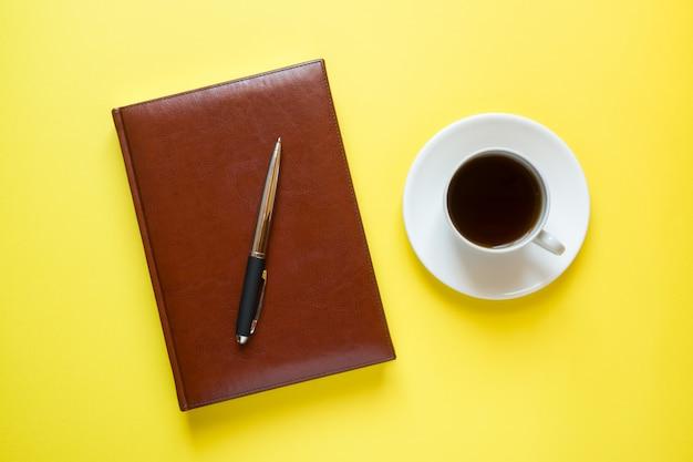 Tagebuch in lederhülle und eine tasse kaffee
