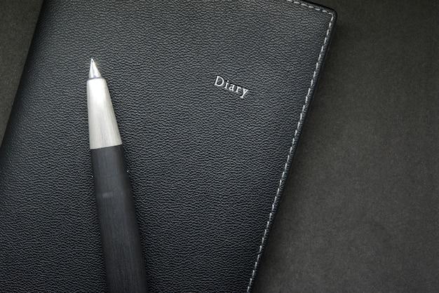 Tagebuch mit füllfederhalter auf schwarzem hintergrund